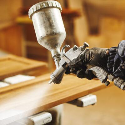 Staining wood with white spray gun, close-up shot. Application of flame retardant ensuring fire protection, airless spraying.