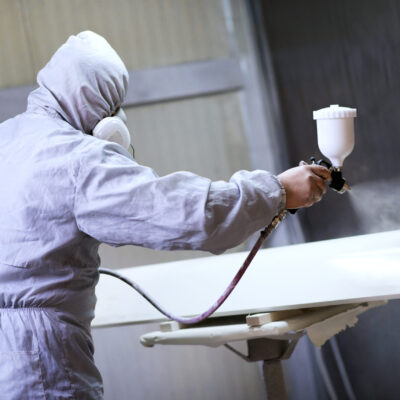 Mechanic in Painting Booth Spray Wooden Part of Furniture or hood of a car.